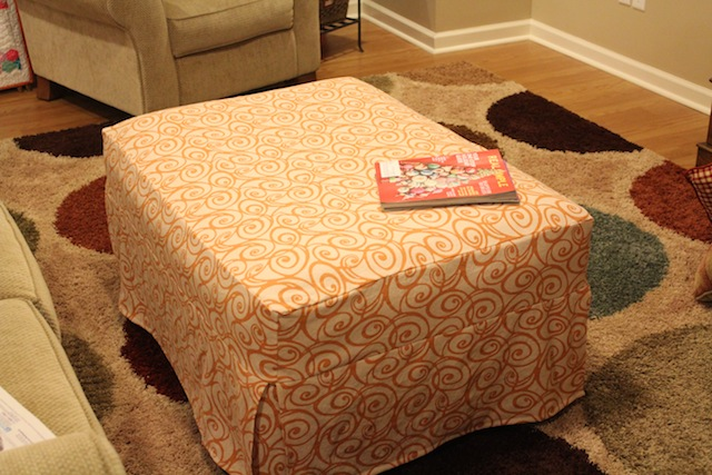 orange slipcovered ottoman