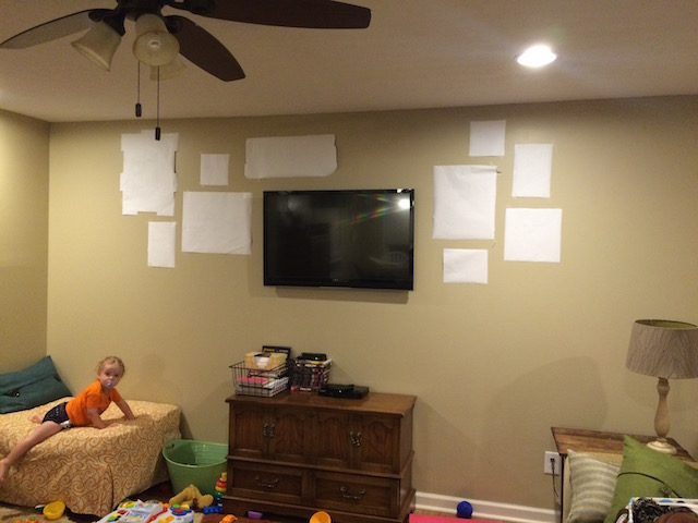 mapping out the gallery wall in the living room with paper