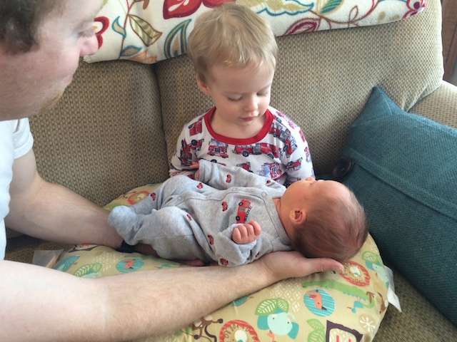 holding new baby brother