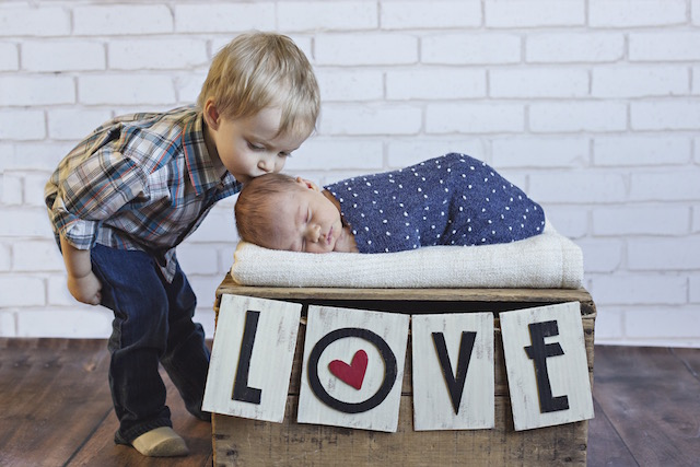 newborn pictures with big brother kisses