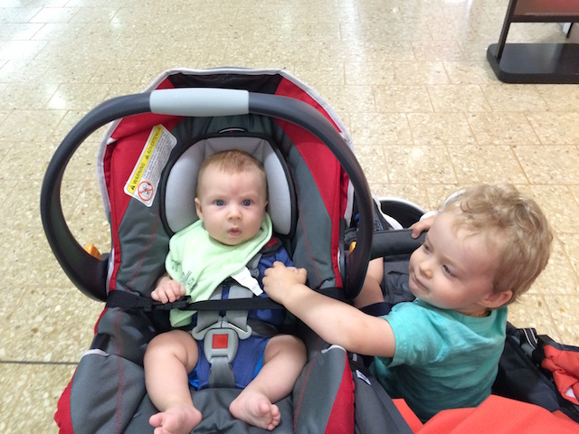 holding hands in the stroller at the mall