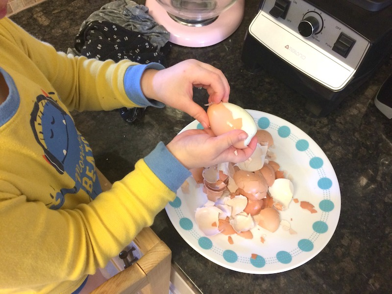 toddler helping to peel boiled eggs